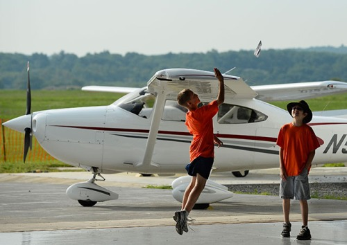 Cub Scout Connor Frazier launches a paper airplane into flight beside a Cessna 182 with Alex Durnal during their Take Flight! summer day camp. Photo by David Tulis/AOPA.